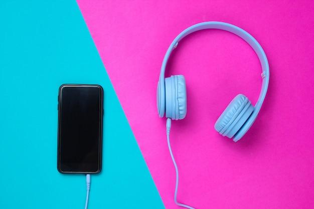 Fones de ouvido conectados ao smartphone em um fundo azul e rosa