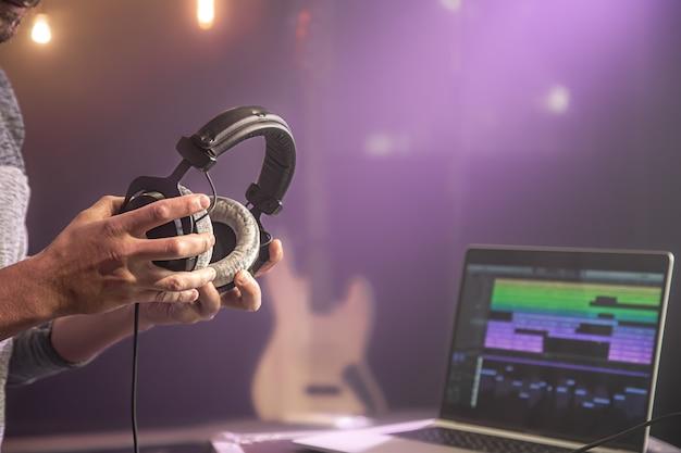 Fones de ouvido de áudio de estúdio para gravar som em mãos masculinas na parede turva do estúdio de música com monitor de laptop close-up.