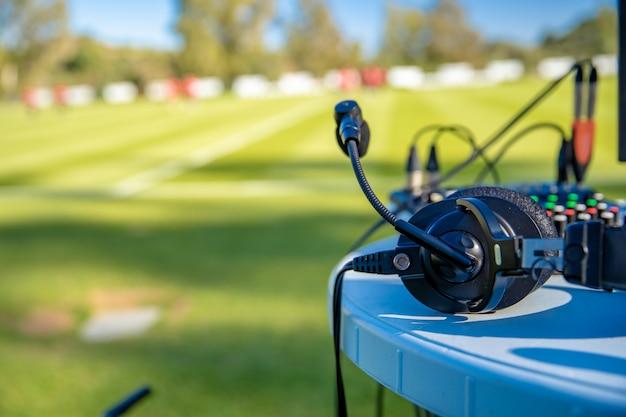 Fones de ouvido de comentarista na mesa ao lado do campo de futebol. transmissão para televisão e rádio