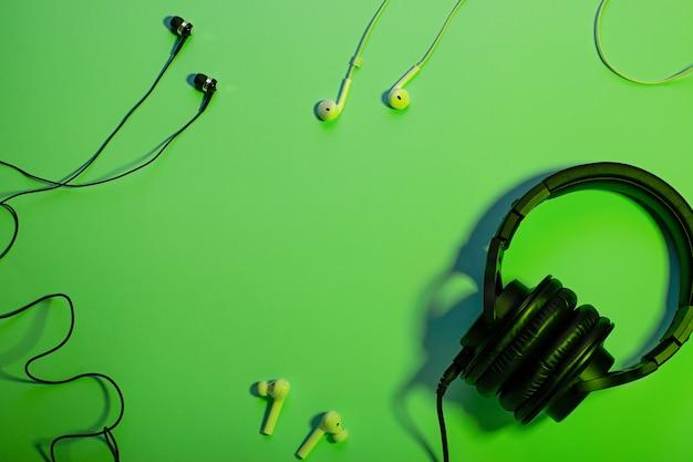 Fones de ouvido de diferentes tipos planos leigos sobre fundo de cor verde, cópia espaço.