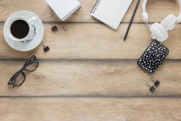 Fones de ouvido de papelaria e café na mesa de madeira