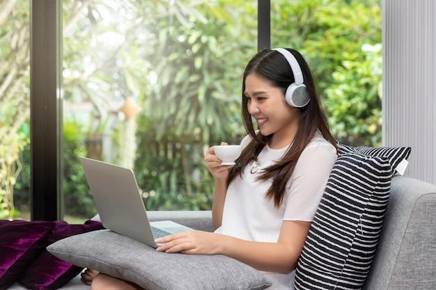 Fones de ouvido do desgaste de mulher que sentam-se no sofá com uma xícara de café e que usam o portátil.