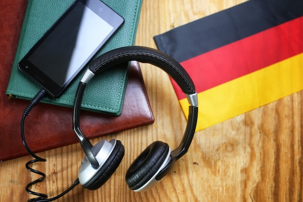 Fones de ouvido e bandeira em uma linguagem de curso de conceito de fundo de madeira