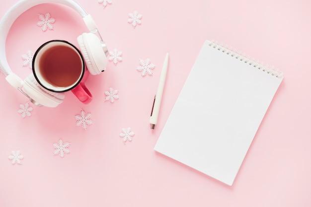 Fones de ouvido e bebidas perto de flocos de neve e o bloco de notas