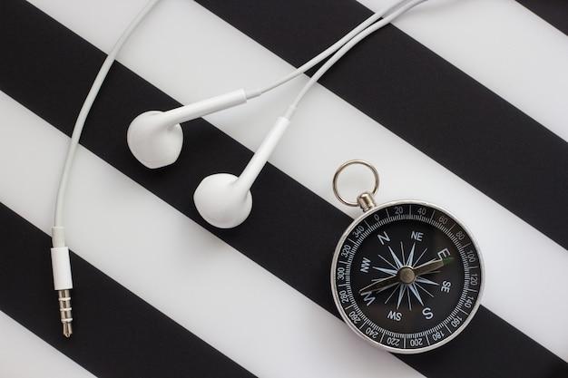 Fones de ouvido e bússola em fundo preto e branco, close-up