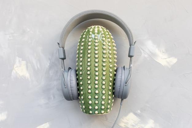 Fones de ouvido e cacto de cerâmica em plano cinza e plano