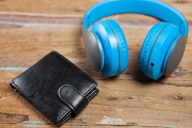 Fones de ouvido e carteira em mesa de madeira