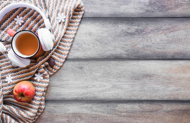 Fones de ouvido e chá perto de apple no cobertor