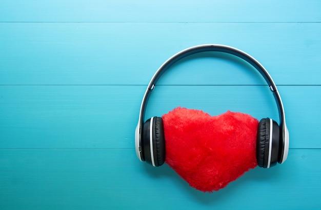 Fones de ouvido e coração escutando música de forma no fundo de madeira azul