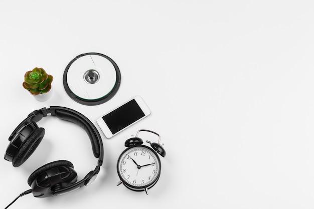 Fones de ouvido e despertador isolados no fundo branco. vista do topo
