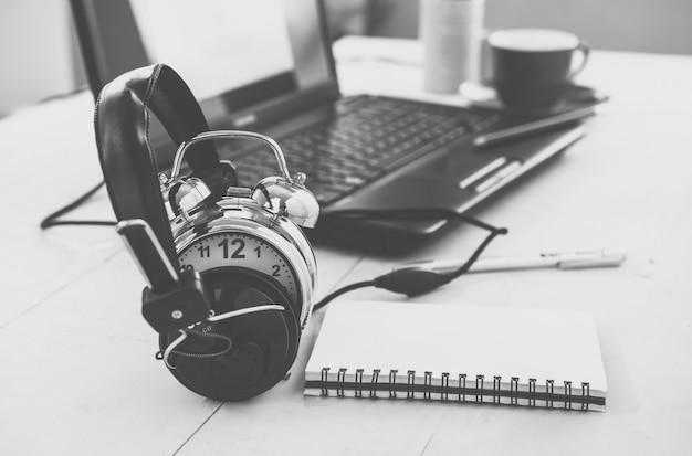 Fones de ouvido e despertador na mesa de trabalho. educação ou relaxar o conceito. tom vintage, efeito de filtro retrô.