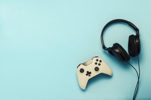 Fones de ouvido e gamepad sobre um fundo azul. . conceito de jogos de computador, entretenimento, jogos, lazer. vista plana leiga, superior.