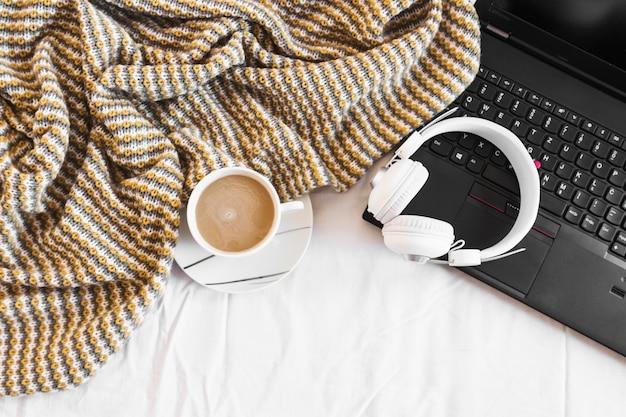 Fones de ouvido e laptop perto de cobertor e café