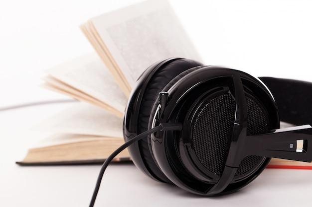 Fones de ouvido e livro sobre um fundo branco