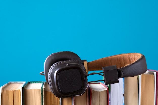 Fones de ouvido e livros, mas contra livros em áudio azuis, ouvindo um livro