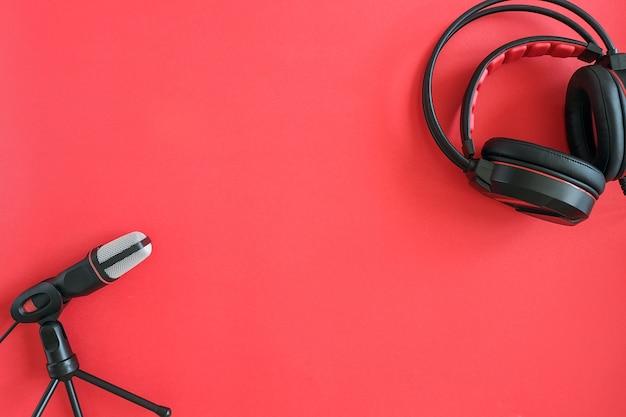 Fones de ouvido e microfone em fundo vermelho. música de conceito ou podcast. vista superior copiar espaço