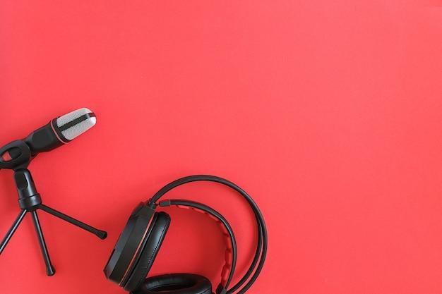 Fones de ouvido e microfone na copyspace vermelho. música conceitual ou podcast. vista superior, configuração plana