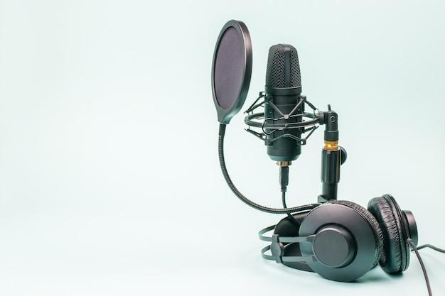 Fones de ouvido e microfone pretos com fios em uma superfície azul clara. equipamento de gravação de som.