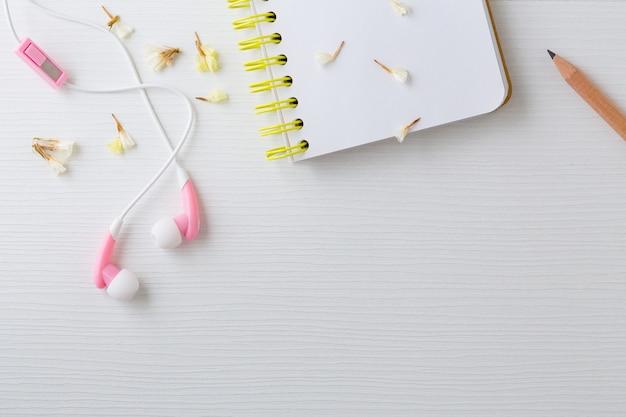 Fones de ouvido e notebook com flores na mesa branca