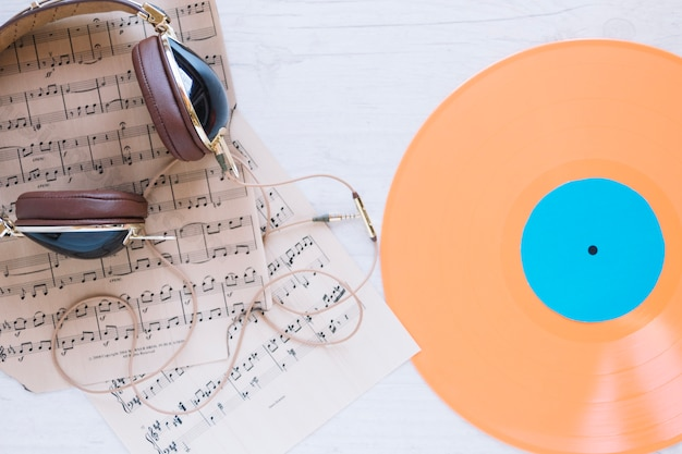 Fones de ouvido e partituras perto de discos de vinil