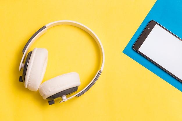Fones de ouvido e smartphone em fundo colorido
