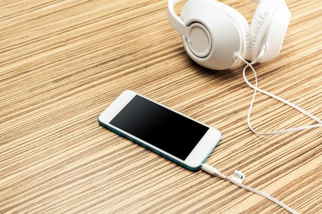 Fones de ouvido e smartphone em madeira
