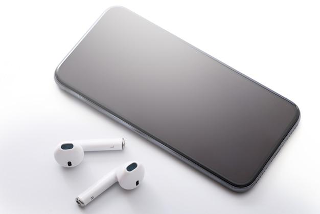 Fones de ouvido e smartphone sem fio na superfície branca