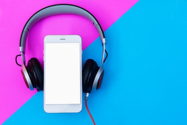 Fones de ouvido e smartphones leigos planos sobre um fundo pastel de cor duotone e espaço da cópia.
