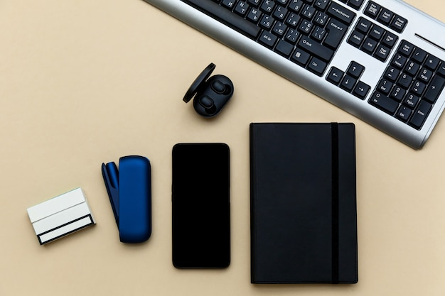 Fones de ouvido e teclado de telefone diário azul iqos de cigarro eletrônico em um fundo bege