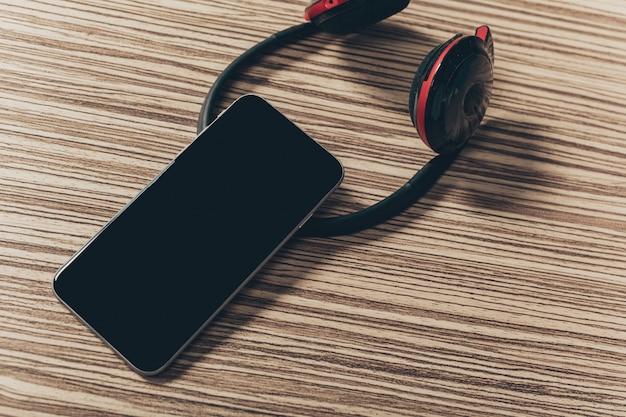 Fones de ouvido e telefone inteligente na madeira