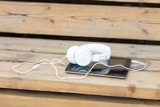 Fones de ouvido e um tablet encontram-se em um banco de madeira no parque em uma noite quente de verão. conceito de caminhada no parque da cidade de verão e ouvir música e estudar.