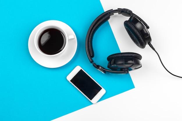 Fones de ouvido e xícara de café sobre fundo azul, vista superior