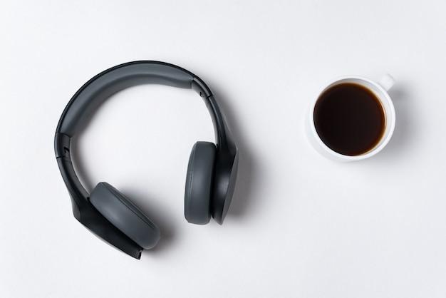 Fones de ouvido e xícara de café, vista superior. minimalismo.