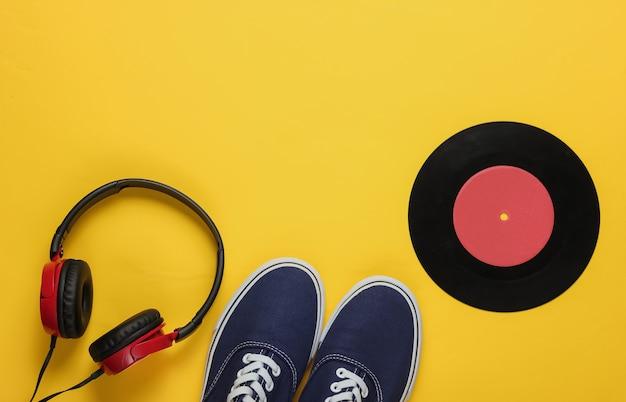 Fones de ouvido elegantes e tênis da velha escola disco de vinil em fundo amarelo
