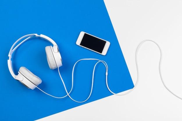 Fones de ouvido elegantes sobre fundo de cor azul e branco, vista superior.