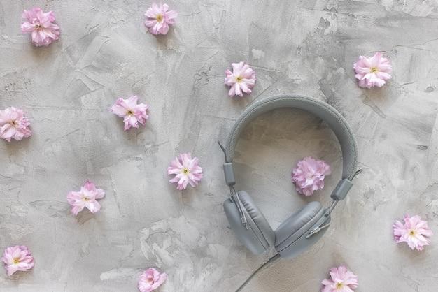 Fones de ouvido em fundo cinza de primavera ou verão