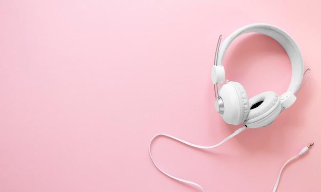 Fones de ouvido em fundo rosa com cópia-espaço