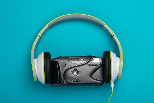 Fones de ouvido estéreo com câmera de filme retrô em uma superfície azul