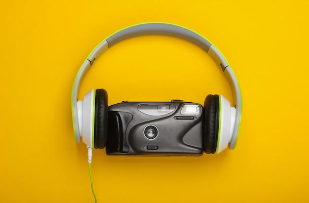 Fones de ouvido estéreo com câmera de filme retrô na superfície amarela