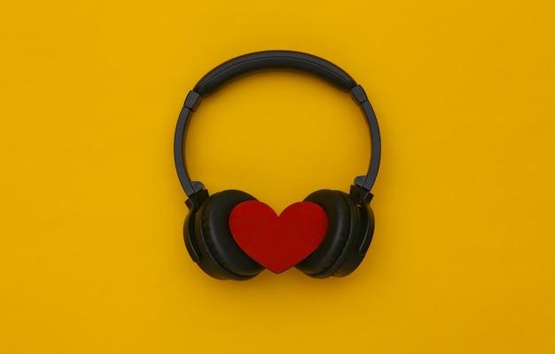 Fones de ouvido estéreo com coração em fundo amarelo. amante da música