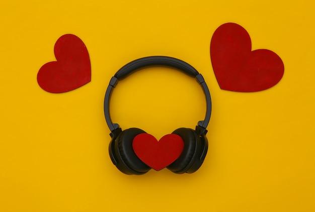 Fones de ouvido estéreo com corações em fundo amarelo. amante da música