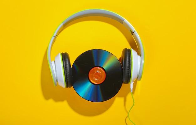 Fones de ouvido estéreo com disco de cd em uma superfície amarela