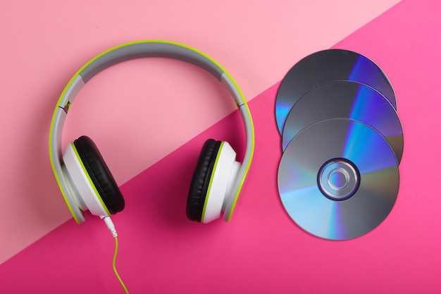 Fones de ouvido estéreo com fio elegantes e discos de cd em superfície rosa pastel