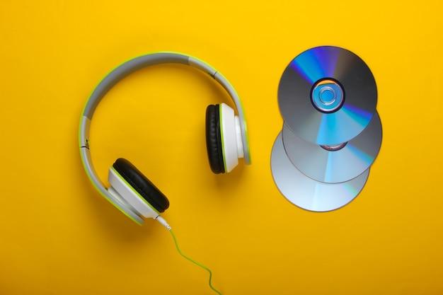 Fones de ouvido estéreo com fio elegantes e discos de cd na superfície amarela