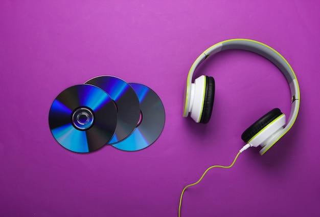 Fones de ouvido estéreo com fio elegantes e discos de cd na superfície roxa