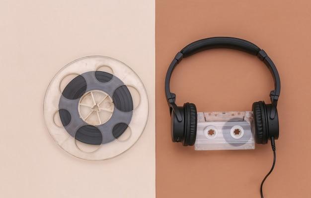 Fones de ouvido estéreo com fita cassete e bobina magnética em fundo bege marrom. vista do topo