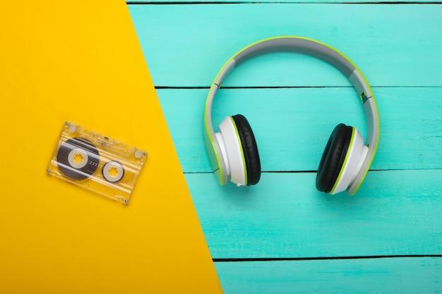 Fones de ouvido estéreo com fita cassete na mesa de madeira azul