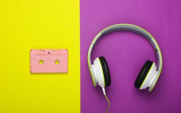 Fones de ouvido estéreo com fita cassete na superfície verde roxa