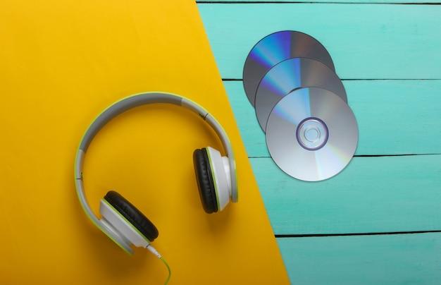 Fones de ouvido estéreo, discos de cd na mesa de madeira azul