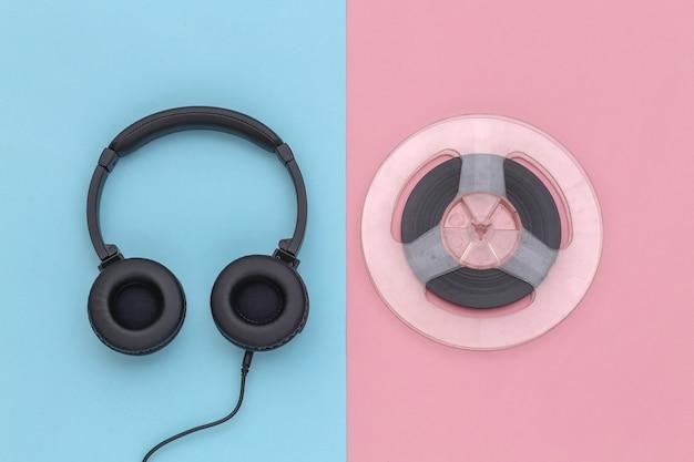 Fones de ouvido estéreo e bobina de áudio magnética em fundo rosa pastel azul. vista do topo